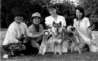 4 women kneeling behing a shikoku with one of them holding a championship ribbon